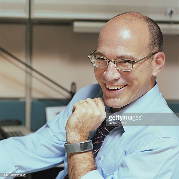 Businessman sitting in cubicle, smiling