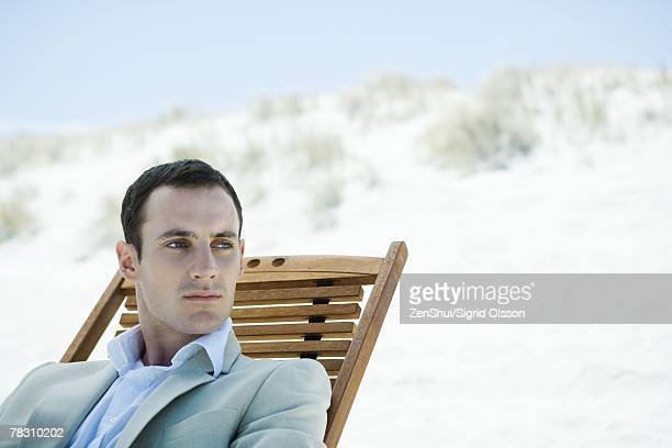 Businessman sitting in deck chair at beach, looking away