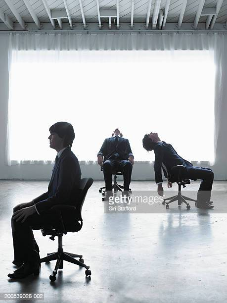 Businessman sitting in different parts of room (Digital Composite)
