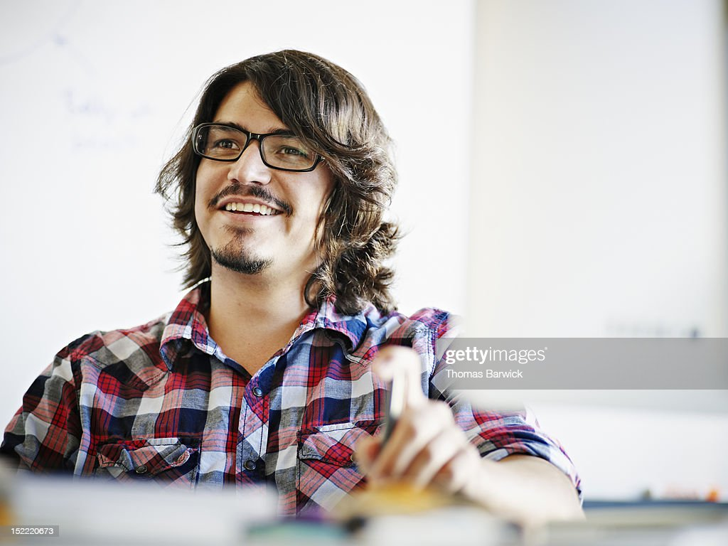 Businessman sitting in discussion at workstation : Stock Photo
