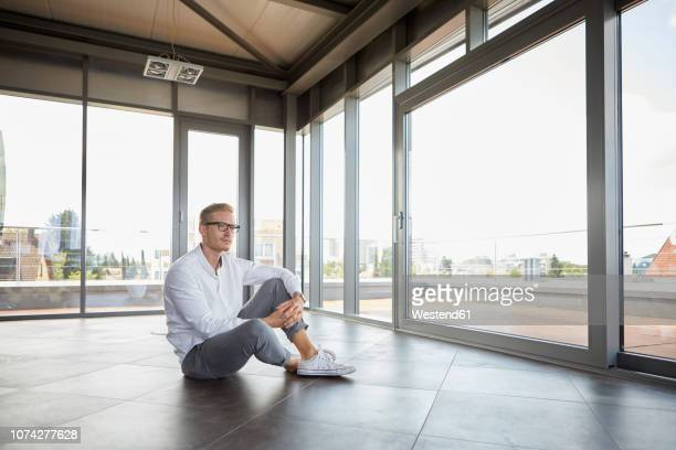 businessman sitting in empty room looking out of panorama window - sitzen stock-fotos und bilder