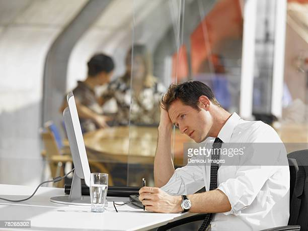 Businessman sitting in front of a desktop PC
