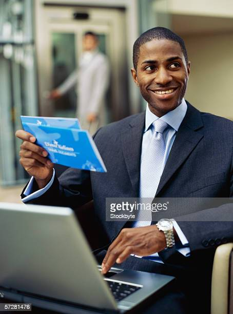 Businessman sitting in front of a laptop holding an airplane ticket