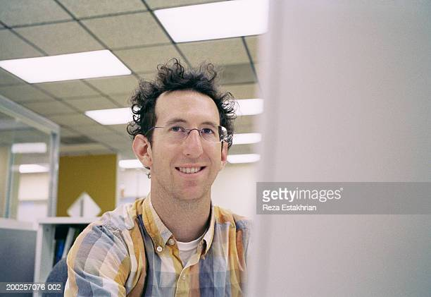 Businessman sitting in front of computer monitor, smiling