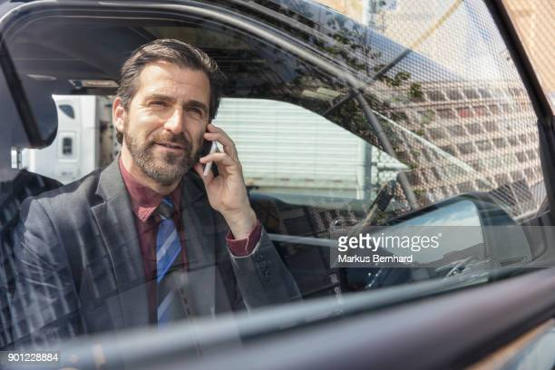 Businessman sitting in his car and talking on mobile