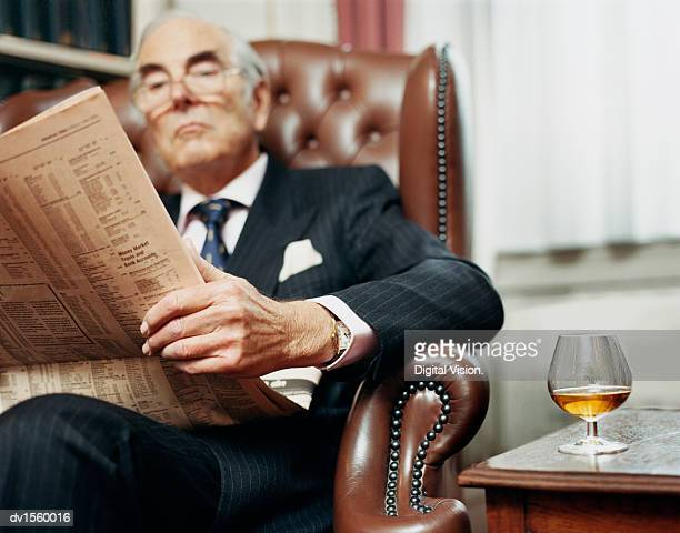 Businessman Sitting in Leather Armchair Next to a Side table, Reading Newspaper