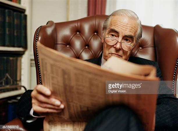 businessman sitting in leather armchair, reading newspaper - striped suit stock photos and pictures