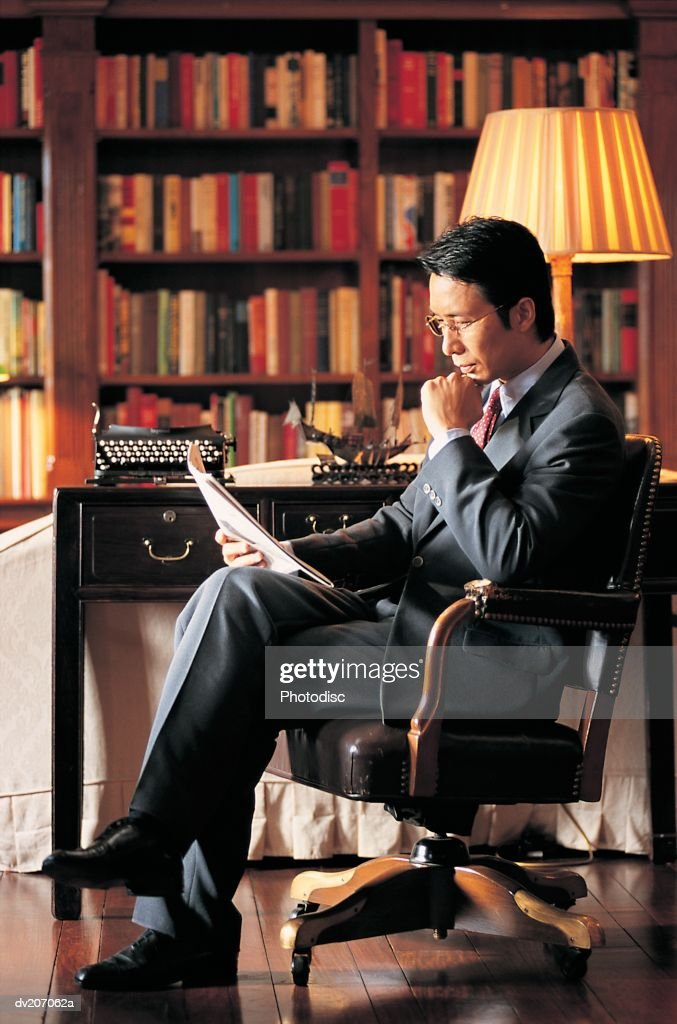 Businessman sitting in library : Stock Photo