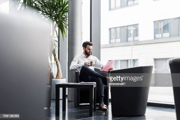 businessman sitting in lobby, drinking coffee, reading documents - focus on background ストックフォトと画像