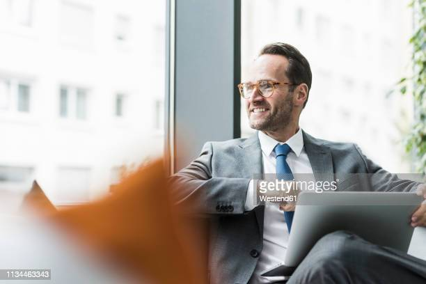 businessman sitting in lobby using laptop - bedrijven financiën en industrie stockfoto's en -beelden