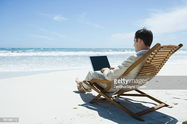 Businessman sitting in lounge chair on beach, barefoot, using laptop