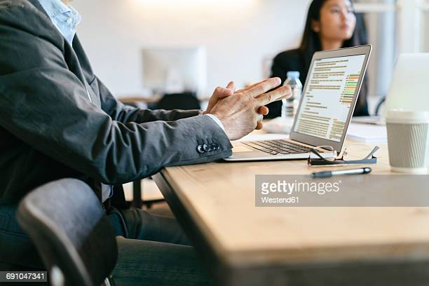 Businessman sitting in meeting, using laptop