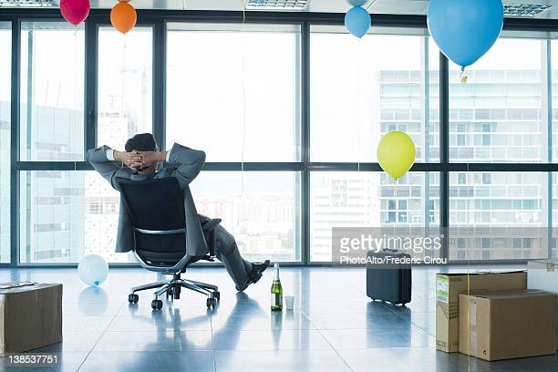 Businessman sitting in new office with balloons and boxes