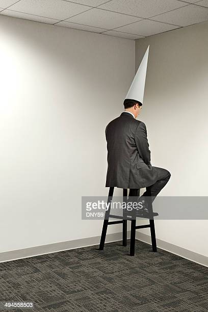 businessman sitting in office corner wearing dunce cap - dunce's hat stock pictures, royalty-free photos & images