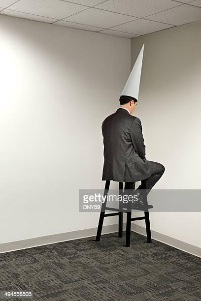 Empresário sentado no canto de escritório vestindo Chapéu de Burro