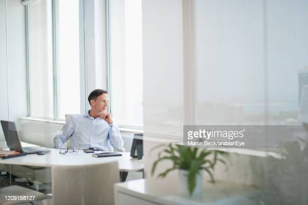 businessman sitting in office in dubai and looking through window. - focus on background stock pictures, royalty-free photos & images
