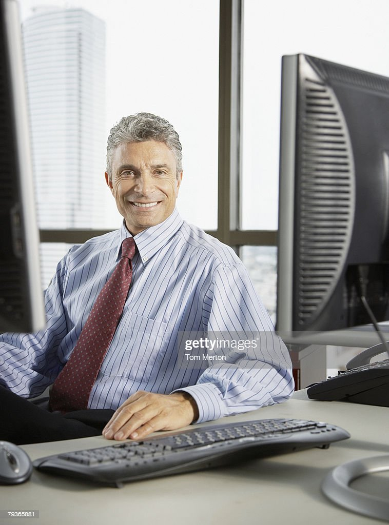 Businessman sitting in office looking at camera : Stock Photo