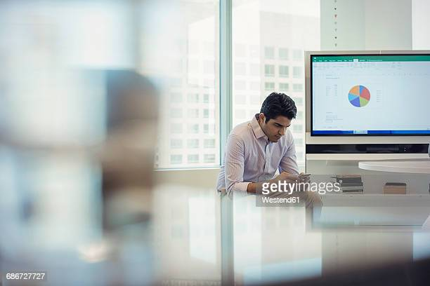 Businessman sitting in office next to screen, checking text messages