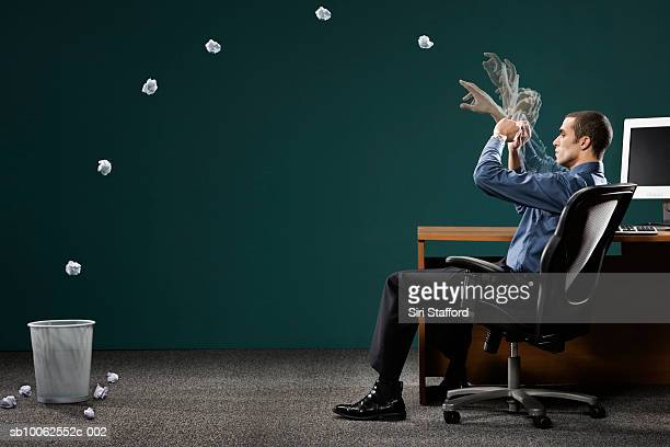 Businessman sitting in office, throwing paper ball in dustbin