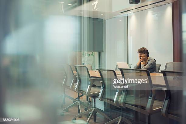 Businessman sitting in office, using laptop