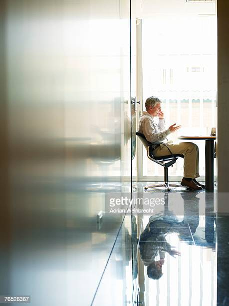 Businessman sitting in office using mobile phone, side view