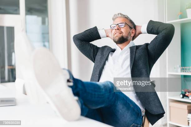 Businessman sitting in office with feet on desk