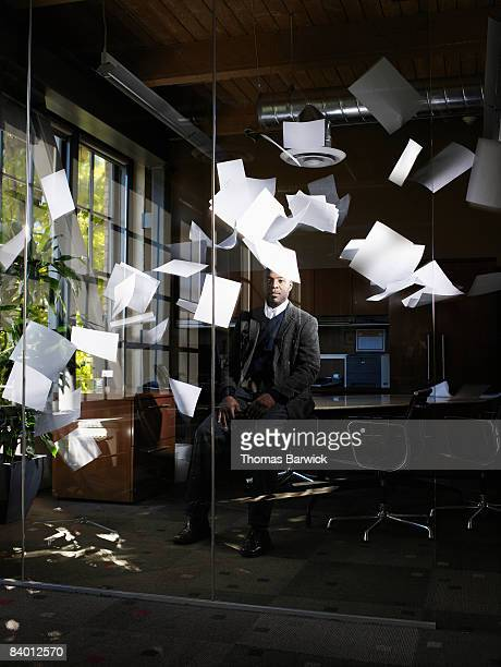 Businessman sitting in office with papers falling