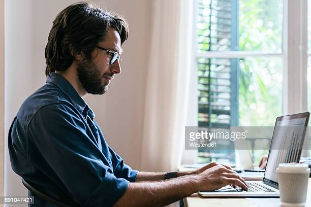 Businessman sitting in office, working at laptop
