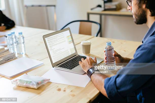 Businessman sitting in office working on laptop