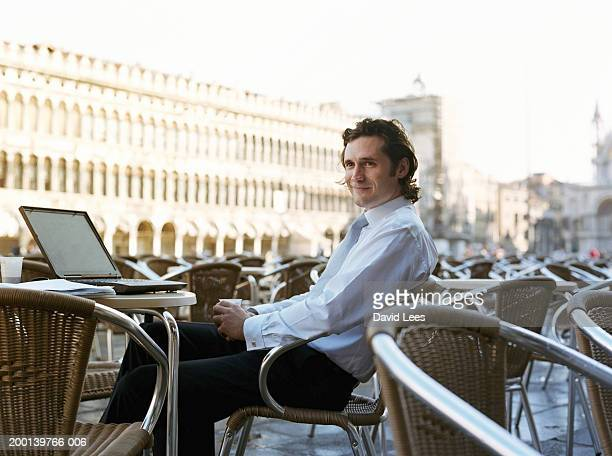Businessman sitting in outdoor cafe with laptop, smiling