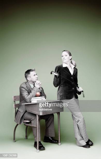 businessman sitting in school desk with female teacher holding whip - women whipping men stock photos and pictures