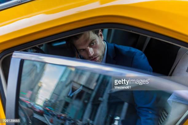 businessman sitting in taxi, using smart phone - イエローキャブ ストックフォトと画像