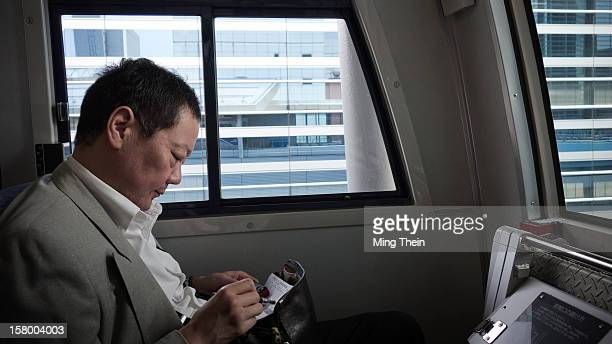 Businessman sitting in the front seat of the automated Odaiba Line train in Tokyo making notes