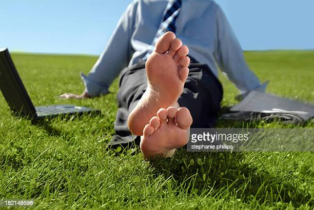 Businessman Sitting in the Grass with Bare Feet