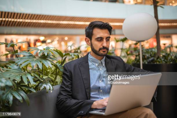 businessman sitting in the office lobby - nosotroscollection stock pictures, royalty-free photos & images