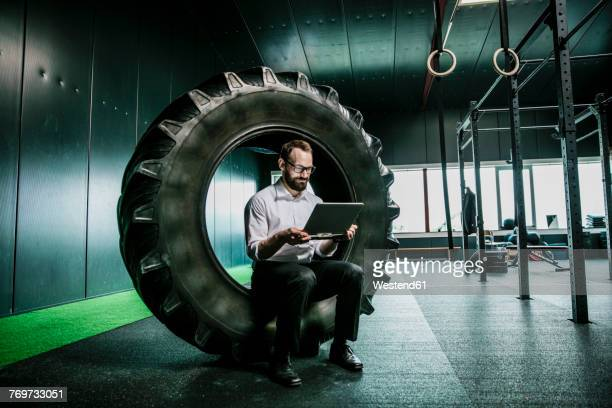 businessman sitting in truck tire in a gym, using laptop - man made structure stock pictures, royalty-free photos & images