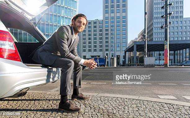Businessman sitting in trunk of station wagon.
