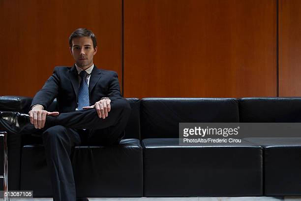 Businessman sitting in waiting room, portrait