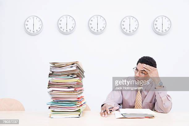 Businessman sitting next to stack of documents on desk, clocks on wall behind