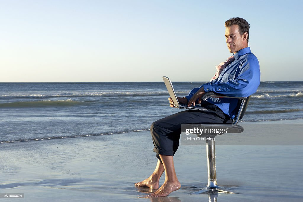 Businessman Sitting on a Beach by the Sea in a Swivel Chair and Looking at the View : Stock Photo