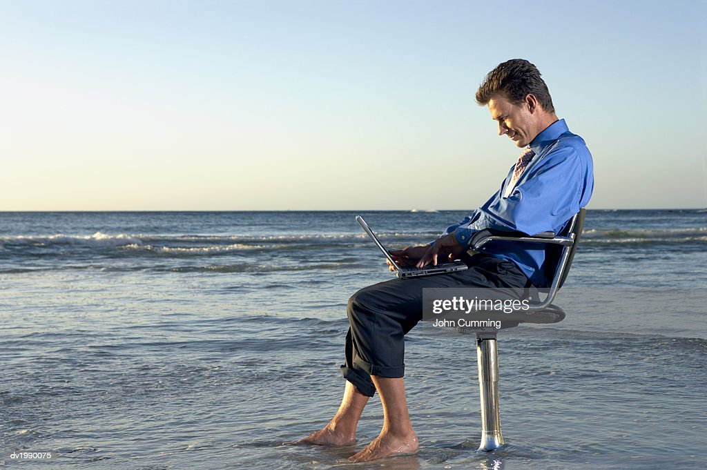 Businessman Sitting on a Beach by the Sea in a Swivel Chair and Working on His Laptop : Stock Photo