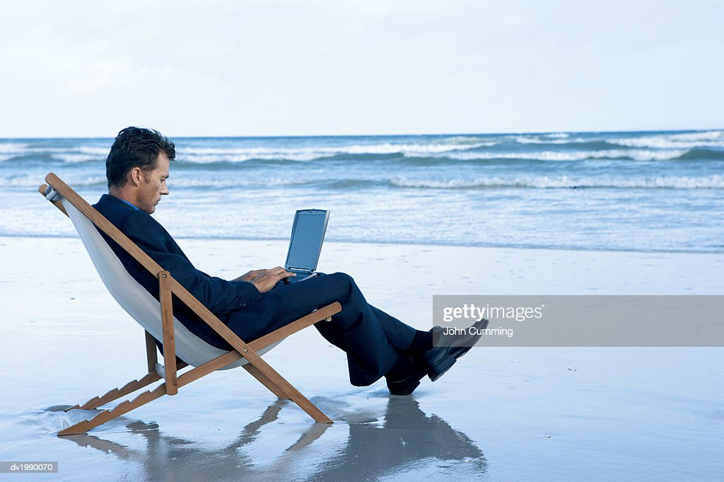 Businessman Sitting on a Beach in a Deck Chair Working on His Laptop : Stock Photo