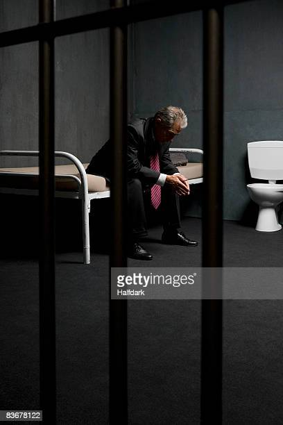 A businessman sitting on a bed in a prison cell