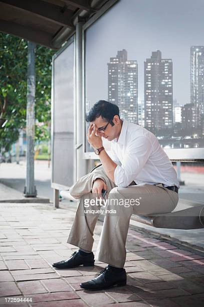 Businessman sitting on a bench at bus stop and looking thoughtful