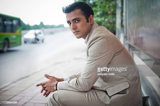 Businessman sitting on a bench at bus stop