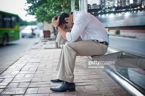 Businessman sitting on a bench at bus stop with his head in hands