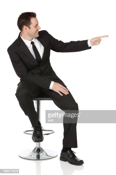 Businessman sitting on a chair and pointing