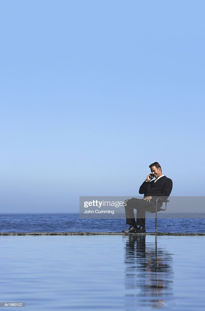 Businessman Sitting on a Chair by the Sea and Using a Mobile Phone : Stock Photo