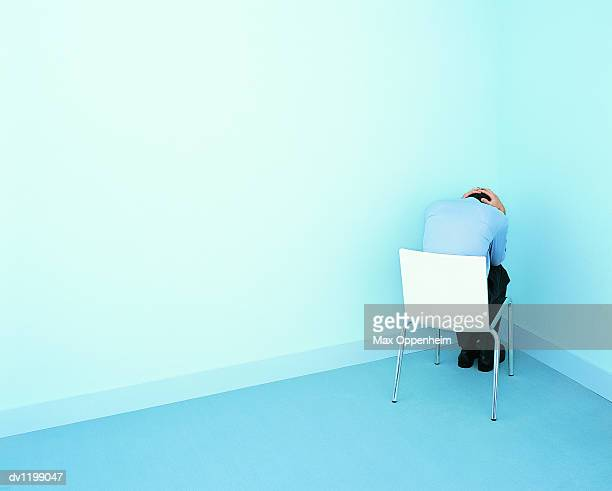 businessman sitting on a chair in a corner looking down with his hands behind his head - ausschluss stock-fotos und bilder