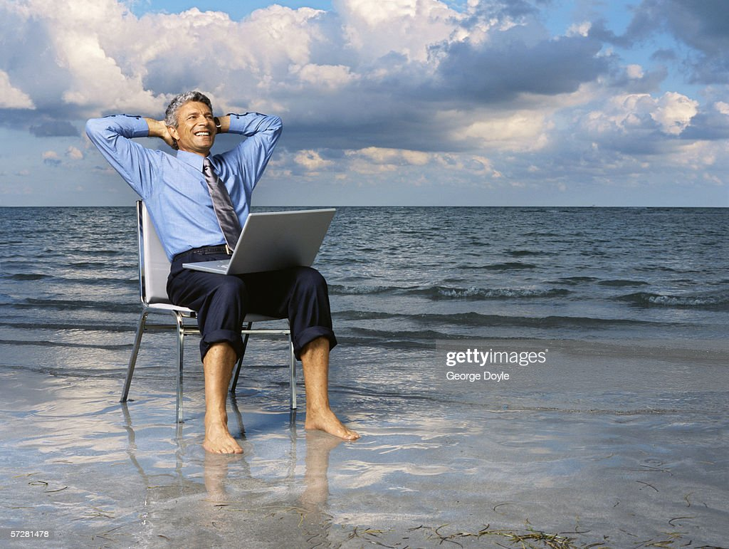 Businessman sitting on a chair on the beach with his hands behind his head : Stock Photo